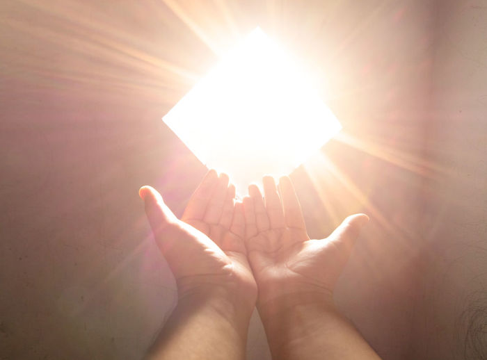 Midsection of person against bright sun