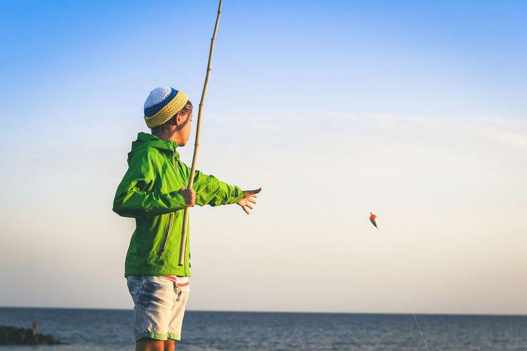 Boy fishing in sea against sky