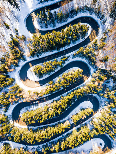 Aerial view of road amidst forest during winter