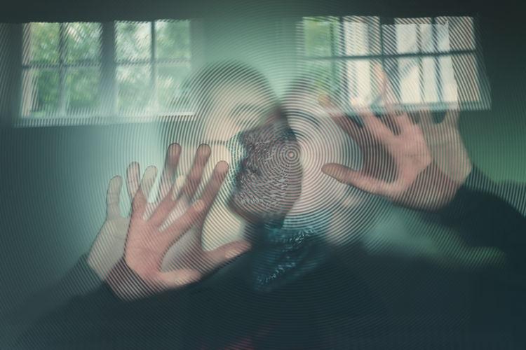 Digital composite image of hand on window