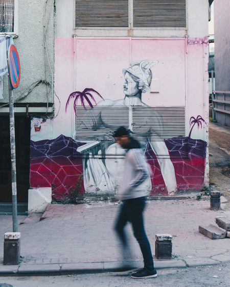 Double meaning, a blurred image of a man walking by a graffiti painting of Hermes on the wall - IG: @LostBoyMemoirs Streetwise Photography Streetphotography Street Photography People People Watching people and places One Person Blurred Motion City Motion Men Art And Craft Graffiti Building Exterior Double Meaning The Art Of Street Photography