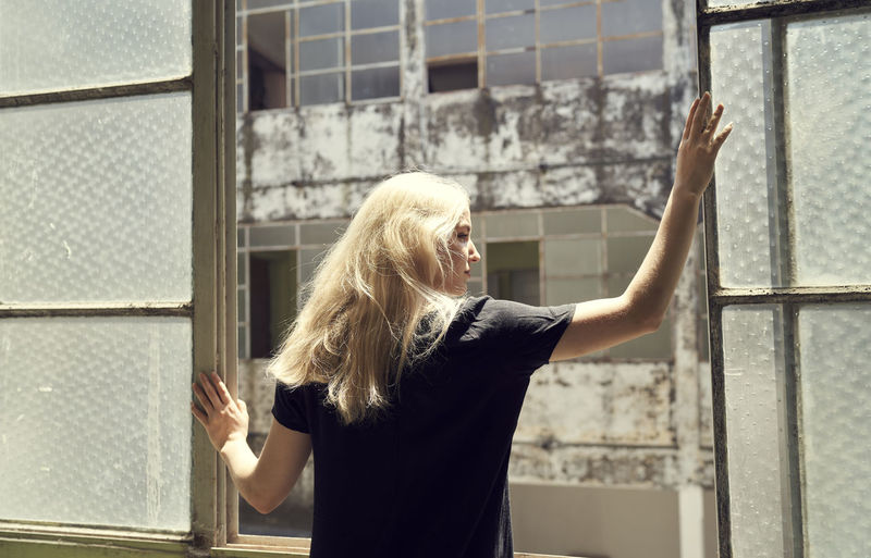 Midsection of woman standing by window