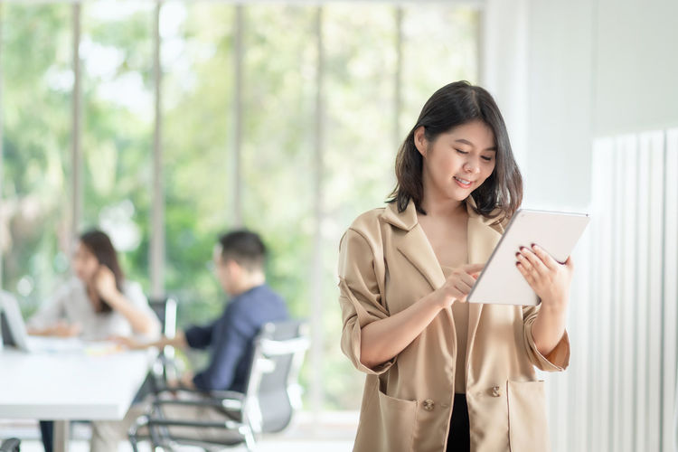 Young woman using phone while standing on laptop