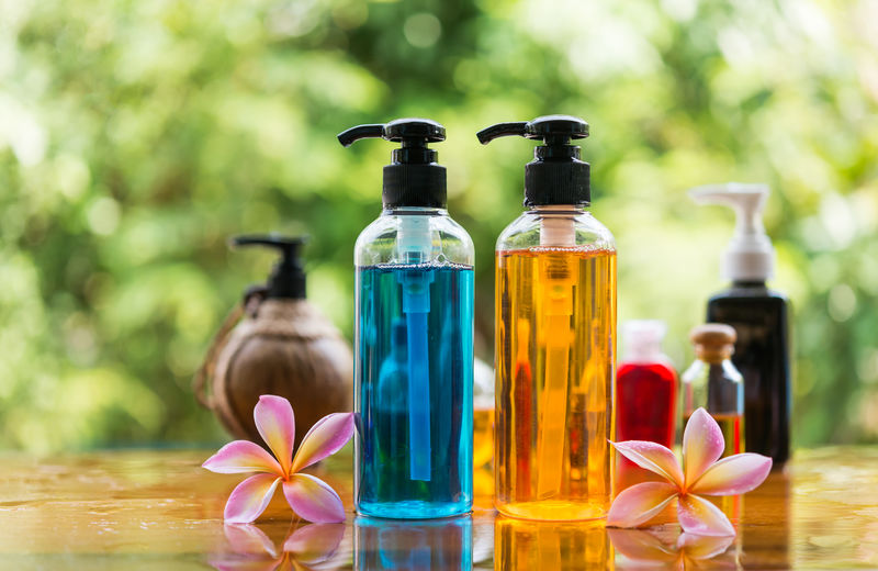 Plumeria Beauty In Nature Body Care Product Bokeh Bottle Container Cosmetics Flower Flowering Plant Focus On Foreground Freshness Gel Bath Green Background Helathy Luxury Outdoors Plant Shampoo Spa Still Life Table Transparent Variation