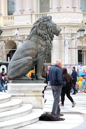 lion, man, dog.skopje oct. 26. 2016 Animal Architecture Balkans Built Structure Day Dog Dog Sleeping  Editorial  History Laying Dog Lion Macedonia Skopje Macedonian Culture Mature Adult People Sculpture Sitting Lion Sitting Outside Skopje Standing Man Statue Statue