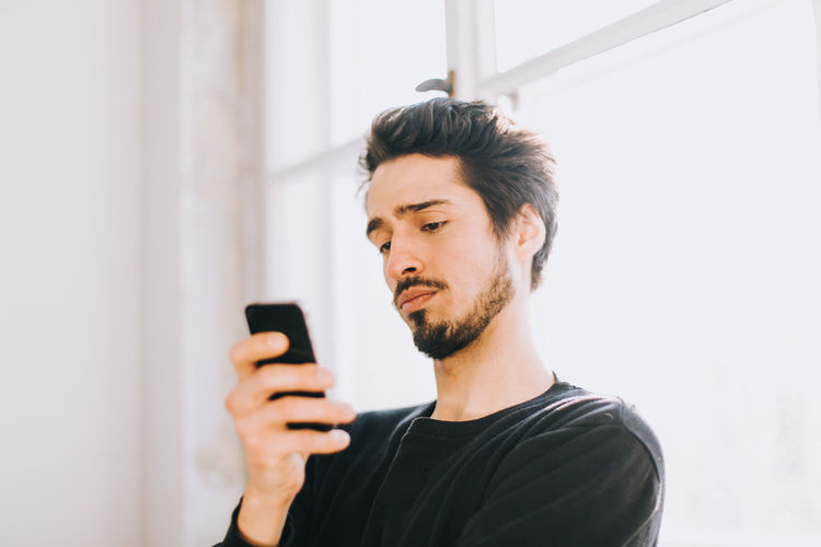 young latino man reading a message on his smartphone Light Man Sunlight Waiting Worried Arab Communication Concerned Handsome Indoors  Latino Lensflare One Person Phone Talk Photo Photography Real Life Real People Sceptical Smartphone Technology Window Window Light