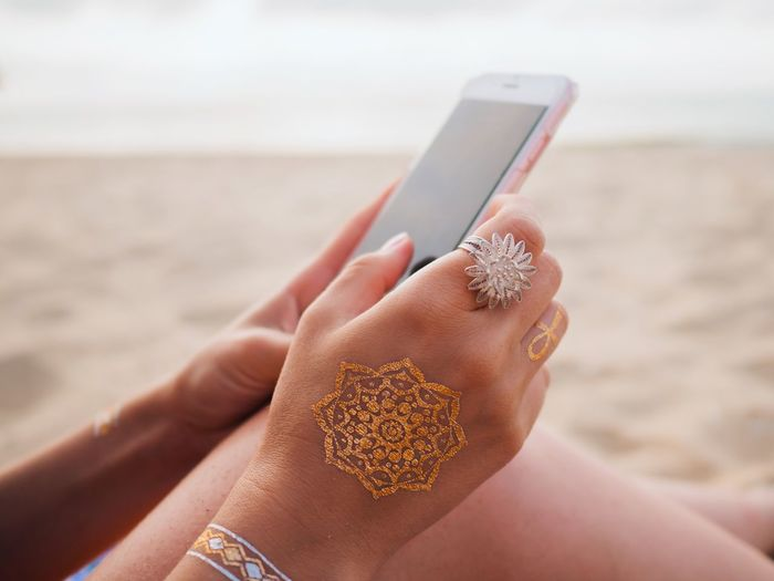 Close-up of woman holding mobile phone at beach