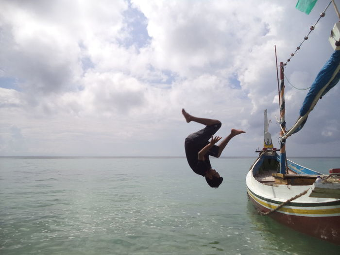 Jump from Boat Backflip Beauty In Nature Boat Cloud - Sky Day Flip Full Length Horizon Horizon Over Water Leisure Activity Lifestyles Nature Nautical Vessel One Person Outdoors Real People Scenics - Nature Sea Ship Sky Transportation Water Waterfront