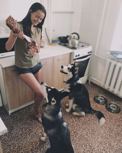Woman with dogs on floor at home
