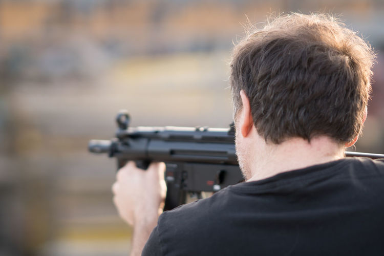 Rear View Of Man Aiming With Rifle