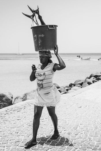 Woman carries Tuna catch from the fish market at Santa Maria on island of Sal in Cape Verde. Travel Woman Working Africa Beach Casual Clothing Fishing Full Length Horizon Over Water One Person Outdoors People Real People Sea Standing Tuna Water