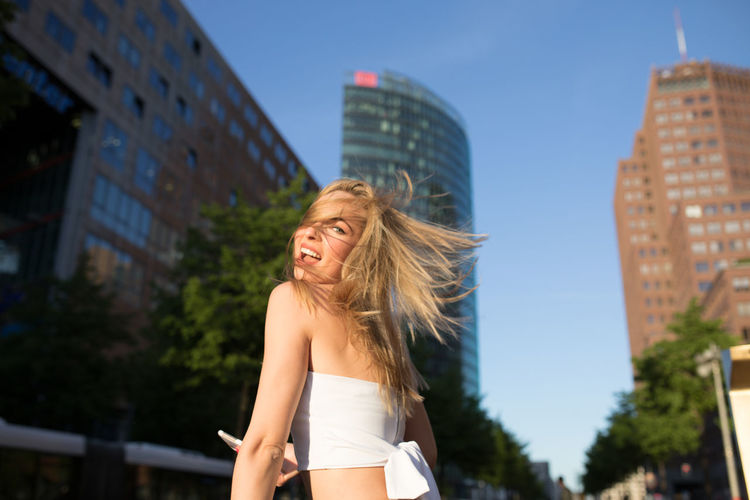 Portrait of happy woman with tousled hair standing against modern buildings in city
