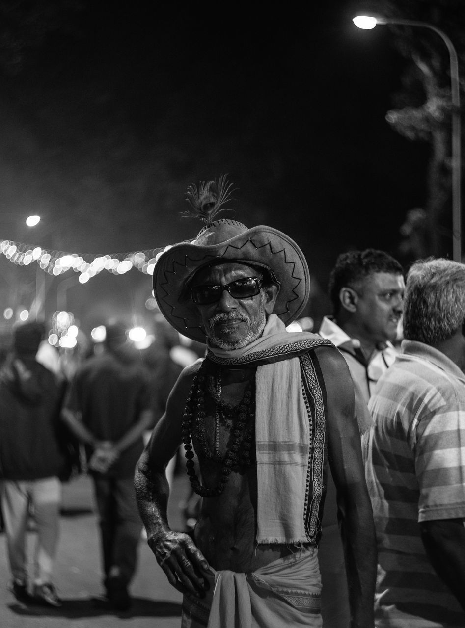 night, real people, togetherness, illuminated, men, focus on foreground, celebration, arts culture and entertainment, lifestyles, leisure activity, enjoyment, outdoors, standing, women, nightlife, friendship, young adult, clown, adult, people