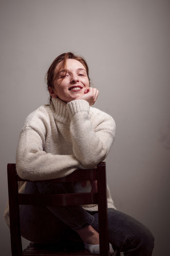 Portrait of smiling young woman sitting on chair against wall