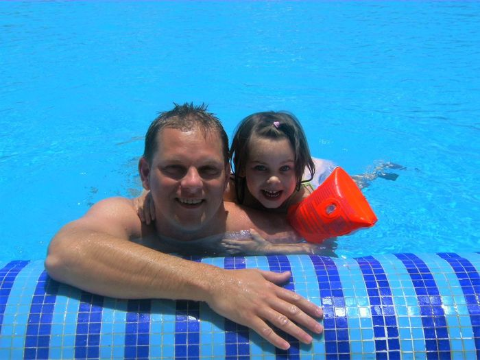 Portrait of father and son swimming in pool