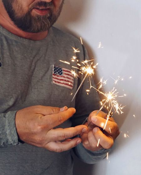 Midsection of man holding illuminated sparkler