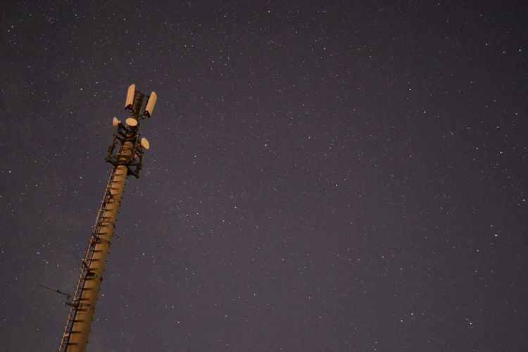 Low angle view of communications tower against star field sky at night