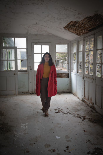 Full length of woman standing by window in building