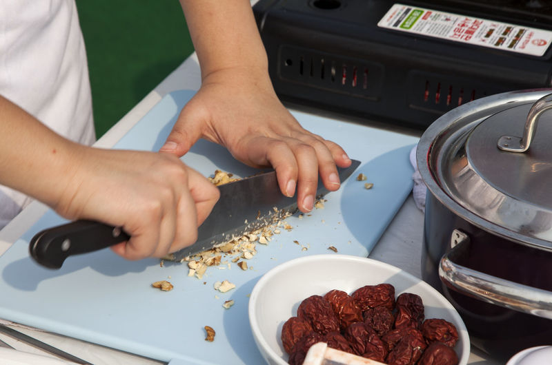 Cropped image of chef chopping nuts at table during cooking competition