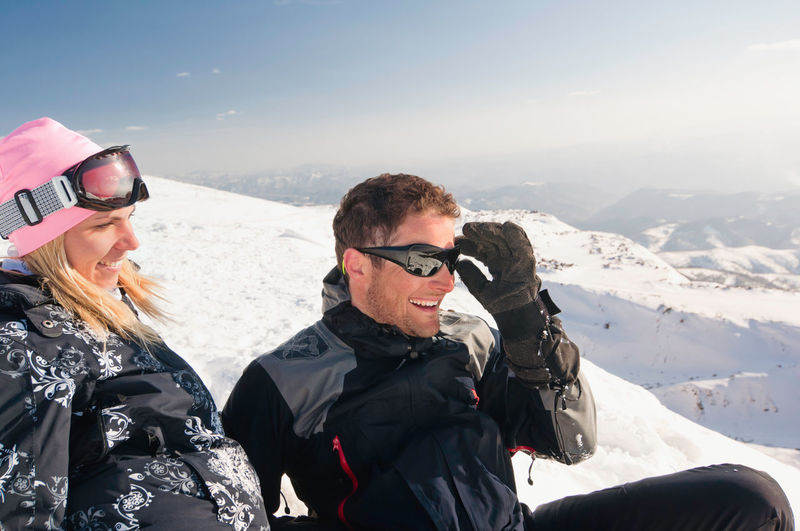 Happy Mid Adult Couple Looking Away On Snowcapped Mountain
