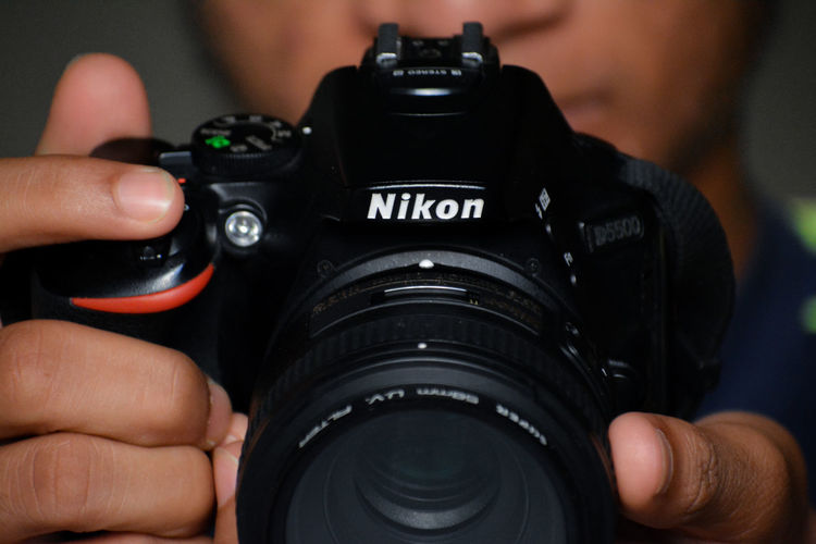 Cropped image of man photographing with camera