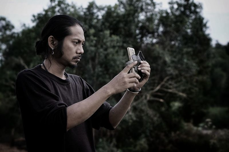 Man photographing with mobile phone while standing against trees