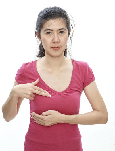 Woman touching breast while standing against white background