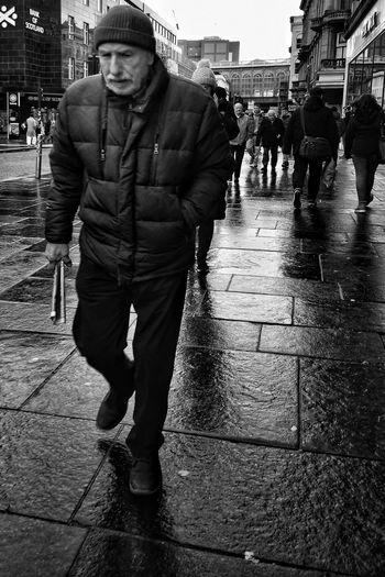 Full length portrait of man standing on wet street