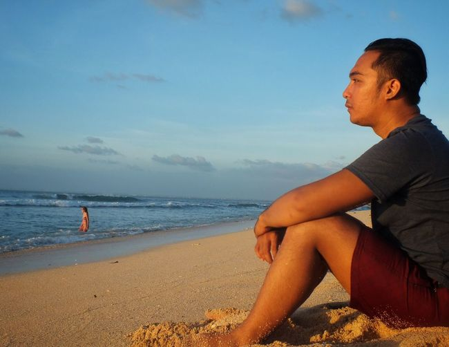 Side View Of Man Sitting On Beach Against Sky