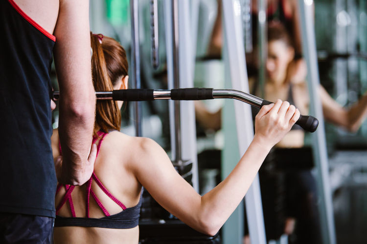 Midsection of trainer assisting woman in exercising at gym