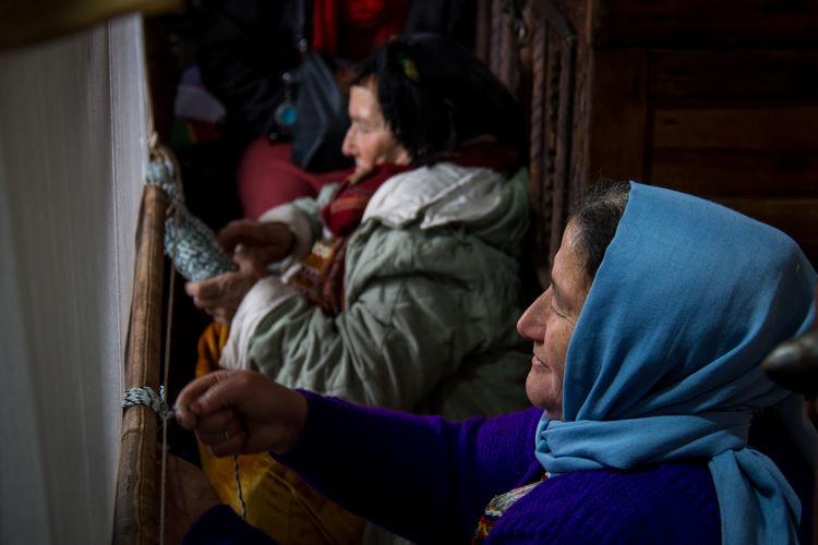 Side view of people weaving loom in workshop