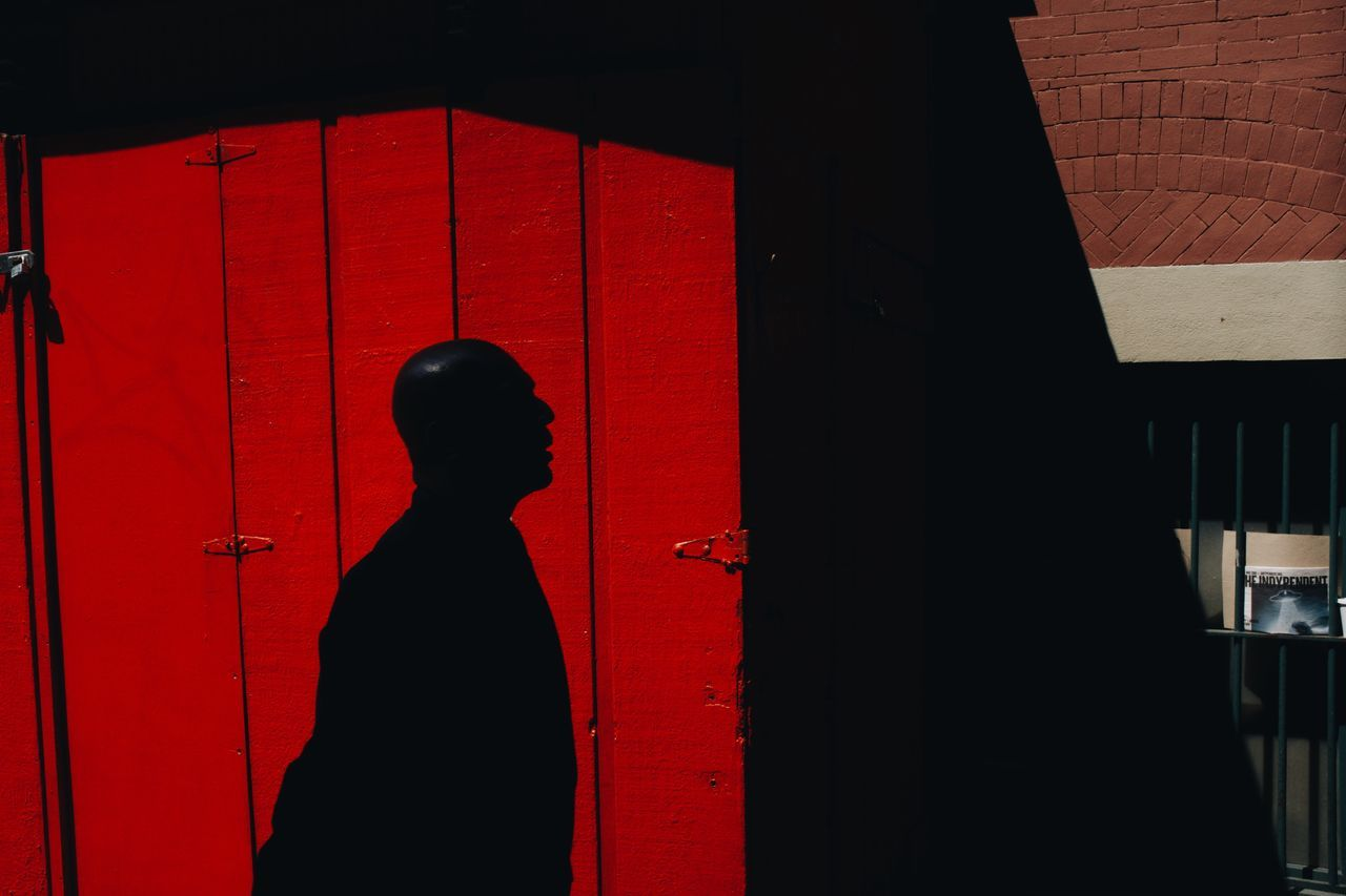 red, one person, real people, standing, lifestyles, entrance, leisure activity, built structure, waist up, sunlight, wall - building feature, architecture, shadow, silhouette, door, indoors, day, men, profile view