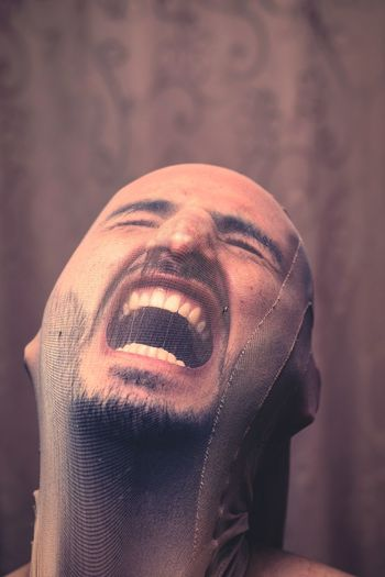 Close-up of man shouting while wearing fabric on face