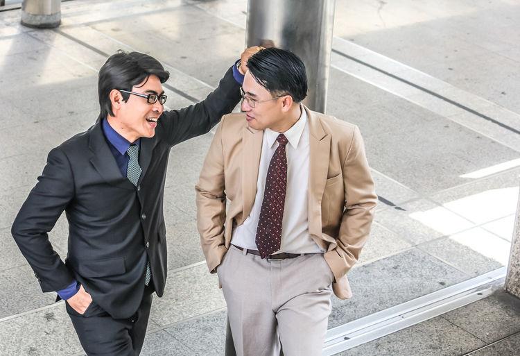 Smiling Businessmen Talking While Standing On Floor