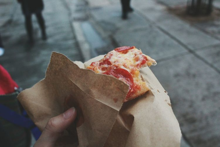 Close-up of hand holding pizza slice