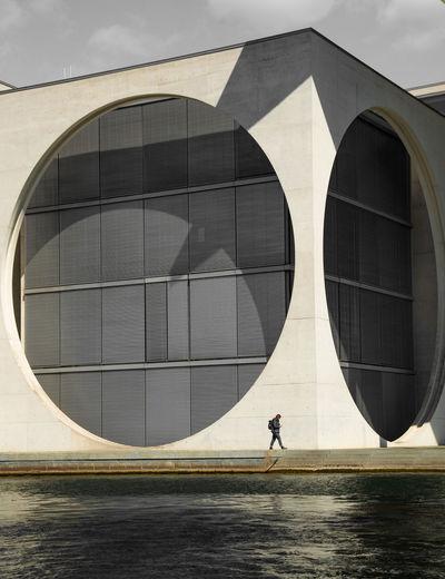 Man walking by modern building in city against sky