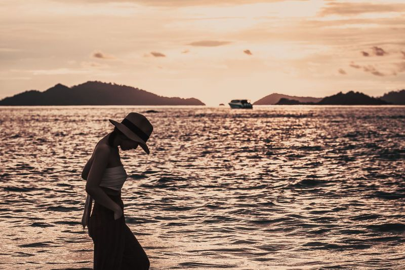 Side view of woman wearing hat standing by sea against sky during sunset