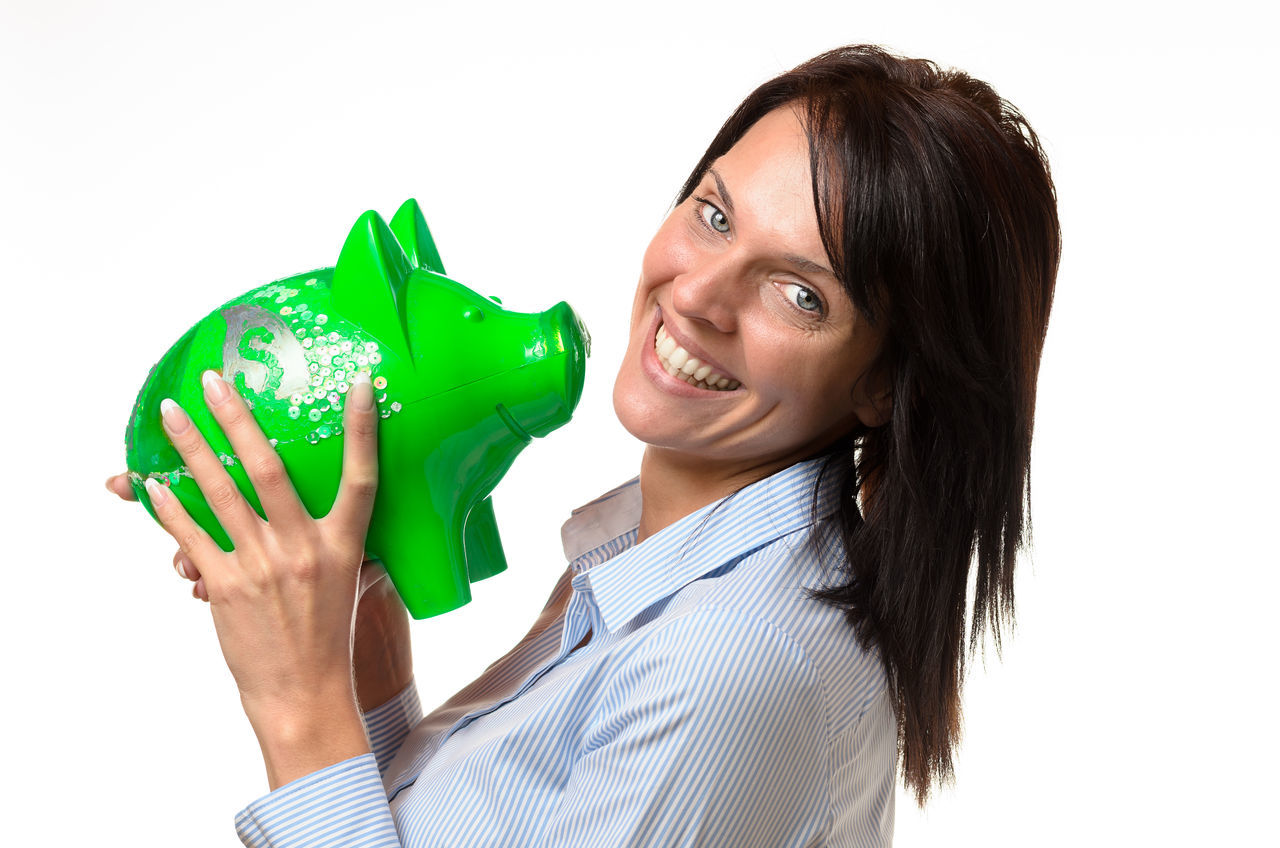 Portrait Of Happy Young Woman With Piggy Bank Against White Background