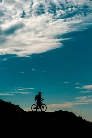 Silhouette person riding bicycle against sky