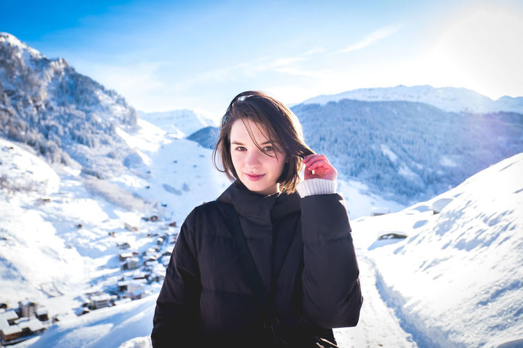 Portrait of woman standing on snowcapped mountains during winter