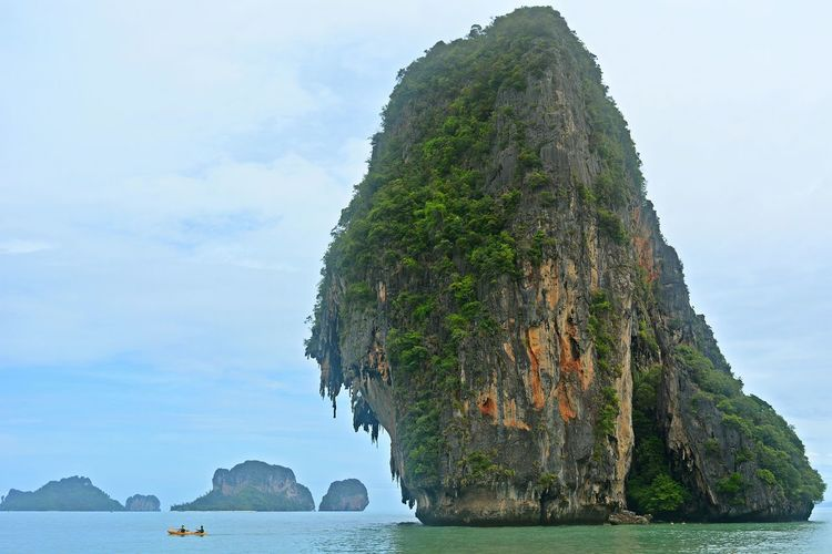 Rock Formation In Sea At Krabi Against Sky