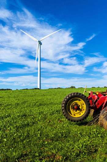 old red agricultural machine on a green meadow with wind turbines on the background of a blue sky in Casares in Spain Field Sky Environment Environmental Conservation Turbine Land Renewable Energy Plant Landscape Wind Turbine Nature Grass Alternative Energy Green Color Day Blue Fuel And Power Generation Wind Power No People Technology Wheel Outdoors Tire Wind Turbine Wind Power Grass Land Nature Rural Scene Green Color