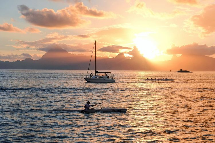 Tahitian rush hour at sunset Nautical Vessel Water Sunset Transportation Mode Of Transportation Sky Sea Beauty In Nature Tranquil Scene Waterfront Sunlight Outdoors Sailing Idyllic Travel Orange Color Cloud - Sky Scenics - Nature Tranquility