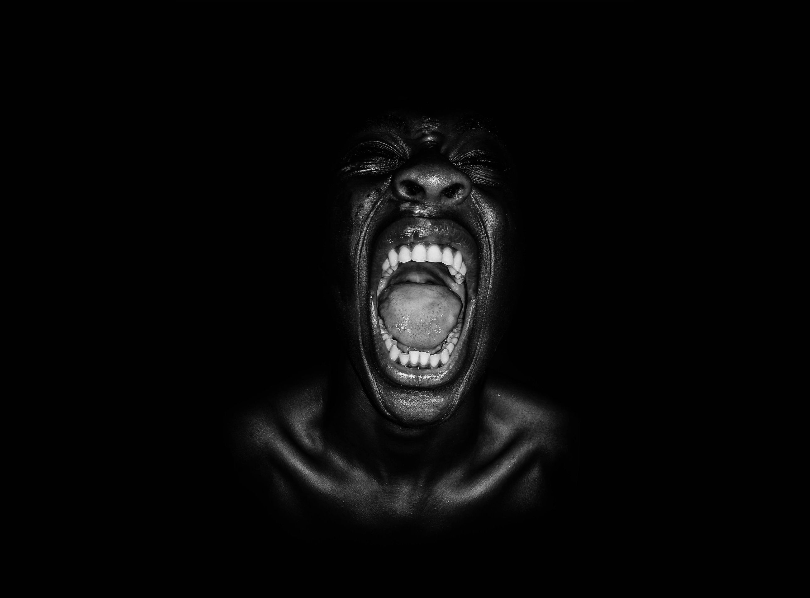 black background, negative emotion, portrait, anger, mouth open, mouth, primate, aggression, shouting, studio shot, frustration, emotion, furious, people, indoors, looking at camera, front view, facial expression, ape, dark, human teeth, human face