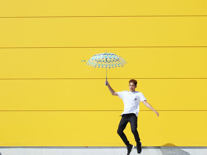 Full length of teenage boy holding umbrella by yellow wall