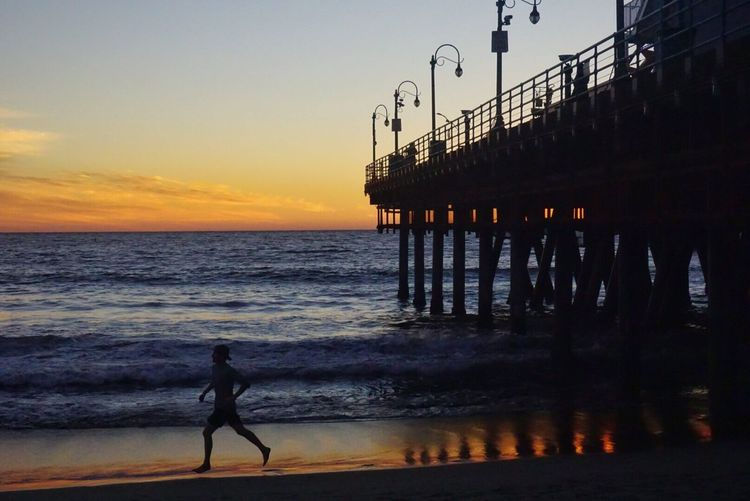 Silhouette Man Running On Shore By Santa Monica Pier At Beach Against Sky During Sunset