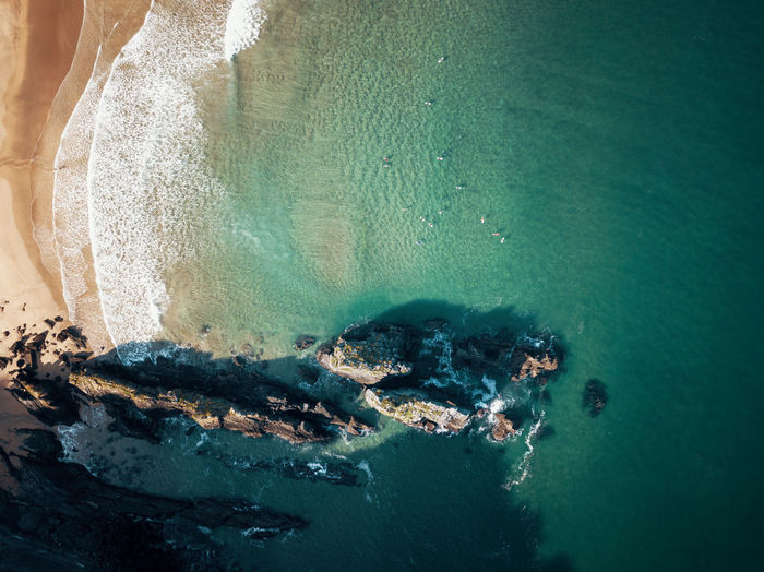 High angle view of surfers and rock in the sea