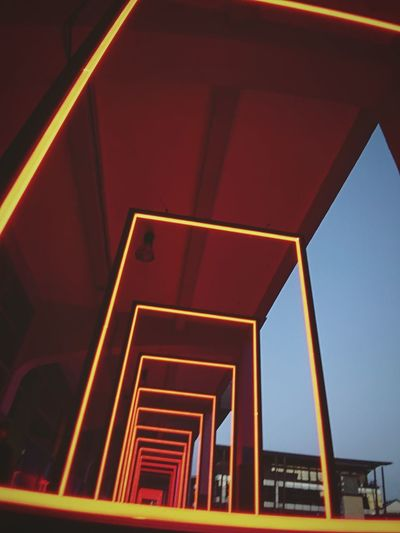 Low angle view of illuminated staircase in building against sky