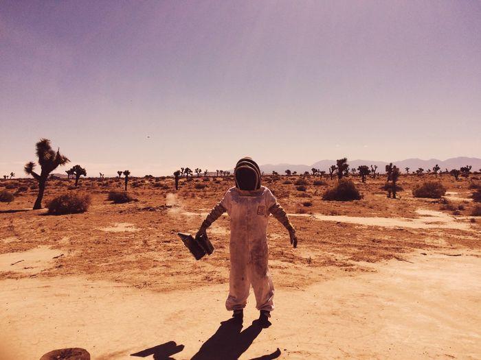 Full length of beekeeper standing in desert against sky