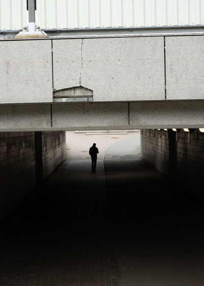 Rear view of silhouette man walking on footpath against building